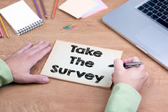 Hand writing Take the Survey. Office desk with a laptop and stat Royalty Free Stock Photo