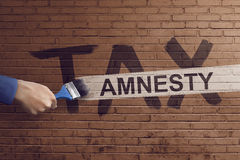 The hand writing tax amnesty. Quotes with a paint brush on the brick wall Stock Image