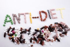 Hand writing text caption inspiration Medical care concept written with pills drugs capsule word ANTI DIET On white. Isolated background with space royalty free stock image
