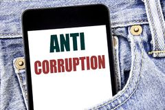 Hand writing text caption inspiration showing Anti Corruption. Business concept for Bribery Corrupt Text written on smartphone in. Jeans pants. Blue background Royalty Free Stock Photos