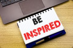 Hand writing text caption inspiration showing Be Inspired. Business concept for Inspiration and Motivation written on notebook boo. K on wooden background in the Stock Photo