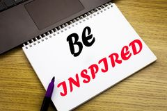 Hand writing text caption inspiration showing Be Inspired. Business concept for Inspiration and Motivation written on notebook boo. K on wooden background in the Royalty Free Stock Photo