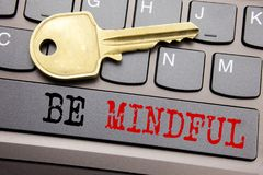 Hand writing text caption inspiration showing Be Mindful. Business concept for Mindfulness Healthy Spirit written on keyboard key. On the key next to the text Stock Image