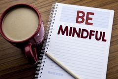 Hand writing text caption inspiration showing Be Mindful. Business concept for Mindfulness Healthy Spirit written on note paper no. Tepad on the wooden Stock Photo