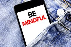 Hand writing text caption inspiration showing Be Mindful. Business concept for Mindfulness Healthy Spirit Written phone mobile pho. Ne, cellphone placed in man Stock Photos