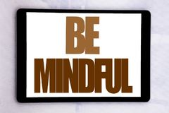 Hand writing text caption inspiration showing Be Mindful. Business concept for Mindfulness Healthy Spirit written on tablet screen. On white background Royalty Free Stock Photography