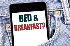 Hand writing text caption inspiration showing Bed Breakfast. Business concept for Holiday Journey Travel written on smartphone in. Jeans pants. Blue background stock photography