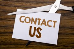 Hand writing text caption inspiration showing Contact Us. Business concept for Customer Support Written on note, wooden back with. Hand writing text caption royalty free stock photo
