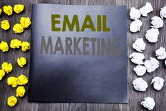 Hand writing text caption inspiration showing Email Marketing. Business concept for Online Web Promotion Written on notepad note n. Otebook wooden background Royalty Free Stock Photo