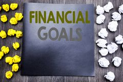 Hand writing text caption inspiration showing Financial Goals. Business concept for Income Money Plan Written on notepad note note. Book wooden background with Stock Images