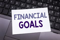 Hand writing text caption inspiration showing Financial Goals. Business concept for Income Money Plan written on sticky note paper. On black keyboard background Stock Photo