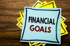 Hand writing text caption inspiration showing Financial Goals. Business concept for Income Money Plan written on sticky note paper. On wooden wood background Stock Photos