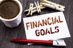 Hand writing text caption inspiration showing Financial Goals. Business concept for Income Money Plan written on sticky note paper. On wooden wood background Stock Images