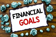 Hand writing text caption inspiration showing Financial Goals. Business concept for Income Money Plan Written on sticky note paper. Wooden background folded Royalty Free Stock Photos