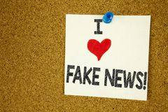 Hand writing text caption inspiration showing I Love Fake News concept meaning Propaganda Newspaper Fake News Loving written on st. Icky note, reminder isolated Stock Photography