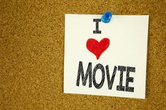 Hand writing text caption inspiration showing I Love Movie concept meaning Entertainment Movie Film Loving written on sticky note, royalty free stock photo