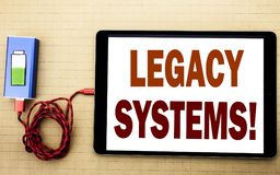 Hand writing text caption inspiration showing Legacy Systems. Business concept for Upgrade SOA Application written on tablet lapto. P with white textured Stock Photos