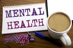 Hand writing text caption inspiration showing Mental Health. Business concept for Anxiety Illness Disorder written on note paper o. N wooden background with stock images
