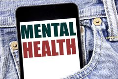 Hand writing text caption inspiration showing Mental Health. Business concept for Anxiety Illness Disorder written on smartphone i. N jeans pants. Blue stock photography