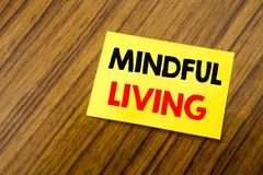 Hand writing text caption inspiration showing Mindful Living. Business concept for Life Happy Awareness written on sticky note pap. Er on wooden keyboard Royalty Free Stock Photography