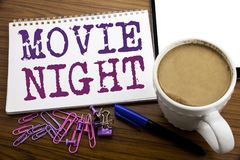 Hand writing text caption inspiration showing Movie Night. Business concept for Wathing Movies written on note paper on the woode. Hand writing text caption stock images
