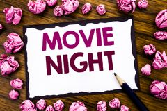 Hand writing text caption inspiration showing Movie Night. Business concept for Wathing Movies Written on sticky note paper, wood. En background folded pink royalty free stock photo