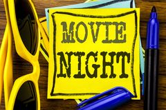 Hand writing text caption inspiration showing Movie Night. Business concept for Wathing Movies Written on sticky note paper, wood. En background vacation stock photos