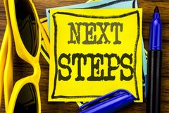 Hand writing text caption inspiration showing Next Steps. Business concept for Future Golas and Target Written on sticky note pape. R, wooden background vacation Royalty Free Stock Images