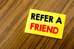 Hand writing text caption inspiration showing Refer A Friend. Business concept for Referral Marketing written on sticky note paper. On wooden keyboard stock image
