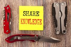 Hand writing text caption inspiration showing Share Knowledge. Business concept for Education Sharing Written on sticky note woode. Hand writing text caption stock photo