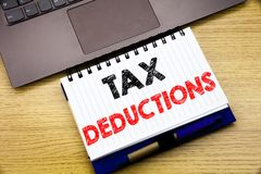 Hand writing text caption inspiration showing Tax Deductions. Business concept for Finance Incoming Tax Money Deduction written on. Notebook book on wooden Royalty Free Stock Image