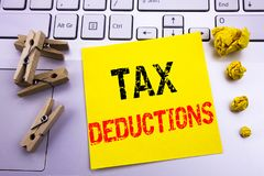 Hand writing text caption inspiration showing Tax Deductions. Business concept for Finance Incoming Tax Money Deduction written on. Sticky paper on the white Stock Image