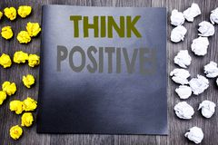 Hand writing text caption inspiration showing Think Positive. Business concept for Positivity Attitude Written on notepad note not. Ebook wooden background with stock images