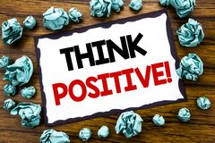 Hand writing text caption inspiration showing Think Positive. Business concept for Positivity Attitude Written on sticky note pape. R, wooden background folded royalty free stock image