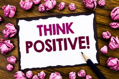 Hand writing text caption inspiration showing Think Positive. Business concept for Positivity Attitude Written on sticky note pape. R, wooden background folded stock image