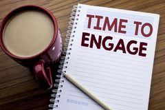 Hand writing text caption inspiration showing Time To Engage. Business concept for Engagement Involvement written on note paper no. Tepad on the wooden Stock Photo