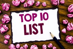 Hand writing text caption inspiration showing Top 10 Ten List. Business concept for Success ten list Written on sticky note paper,. Wooden background folded Royalty Free Stock Photos