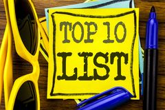 Hand writing text caption inspiration showing Top 10 Ten List. Business concept for Success ten list Written on sticky note paper,. Wooden background vacation Stock Photography