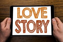 Hand writing text caption Love Story. Business concept for Loving Someone Heart  Written on tablet laptop, wooden background with. Hand writing text caption Love Royalty Free Stock Photo
