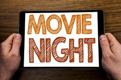 Hand writing text caption Movie Night. Business concept for Wathing Movies Written on tablet laptop, wooden background with busin. Hand writing text caption stock photo