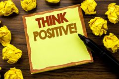 Hand writing text caption showing Think Positive. Business concept for Positivity Attitude Written on sticky note paper, wooden ba. Ckground marker folded yellow stock images