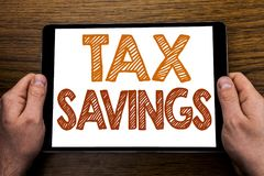 Hand writing text caption Tex Savings . Business concept for Tax Savings Extra Money Refund Written on tablet laptop, wooden backg. Hand writing text caption Tex royalty free stock images