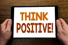 Hand writing text caption Think Positive. Business concept for Positivity Attitude Written on tablet laptop, wooden background wit. Hand writing text caption stock image