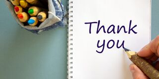 Hand writing `thank you`, isolated on blue background. Bag with pencils