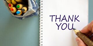 Hand writing `thank you`,  on blue background. Bag with pencils. Concept