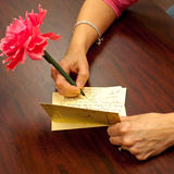 Hand Writing Thank You Note. Woman's hand while writing a thank you note with flowery pen Royalty Free Stock Photos
