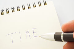 Hand writing 'TIME' on notebook page. Hand writing a 'TIME' on notebook page Royalty Free Stock Photography