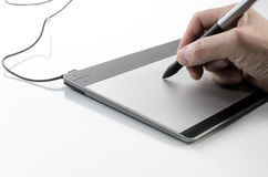 Hand writing on a touch pad. A hand holding a pen against a computer touch pad Stock Photography