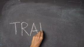 Hand writing TRAINING on black chalkboard. Woman`s hand writing `TRAINING` with white chalk on blackboard stock video footage