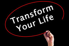 Hand Writing Transform Your Life with a marker over transparent. Board stock image